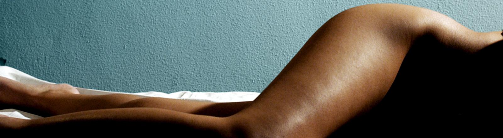 Eine Frau liegt auf der Seite, man sieht ihre Beine und Hüfte.