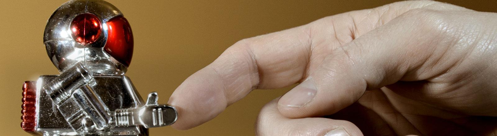 Ein Finger gibt einer kleinen Roboterfigur die Hand.