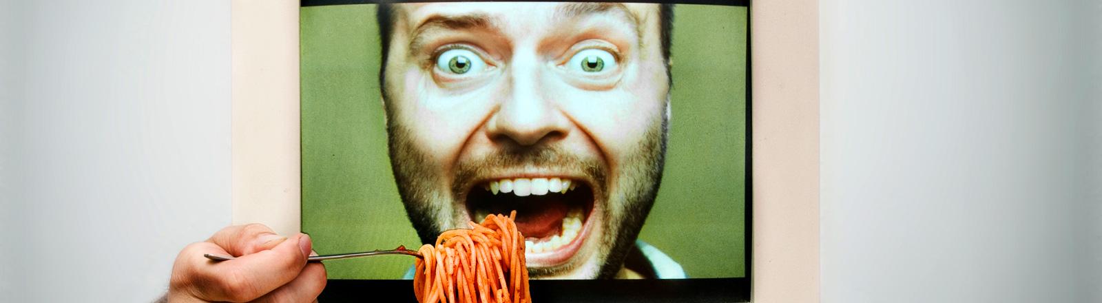 Ein Computer mit dem Gesicht eines Mannes, davor steht ein Teller mit Spaghetti, daneben zwei Hände, die Spaghetti in den Mund schieben.