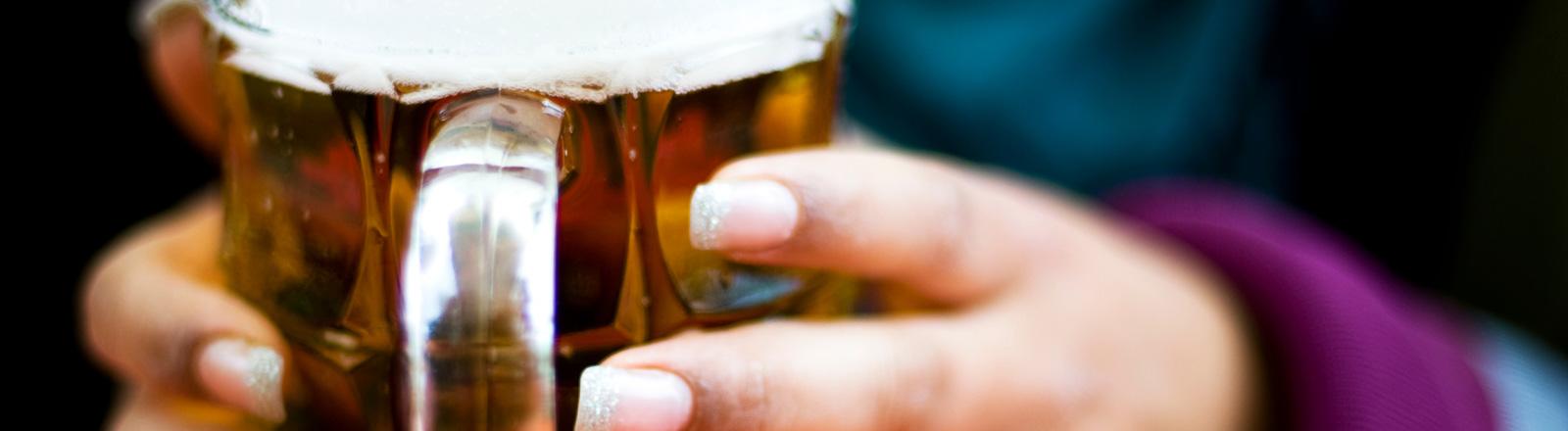 Zwei Hände halten eine Maß Bier.
