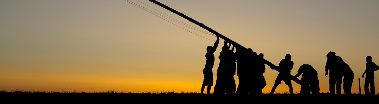 Mehrere Menschen richten gemeinsam einen Mast auf.