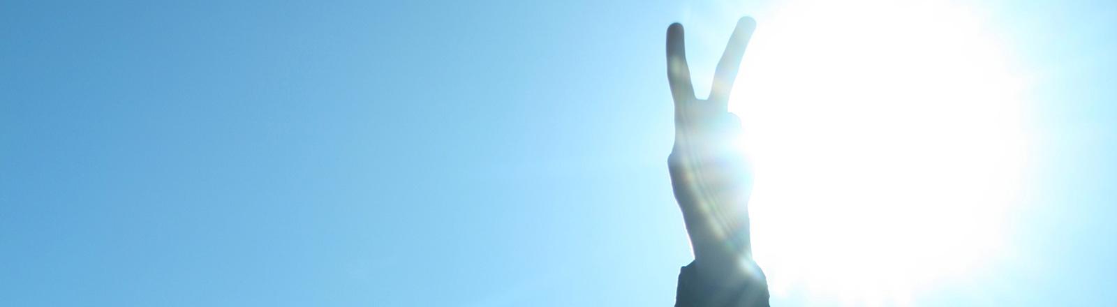 Eine Hand macht das Victory-Zeichen.