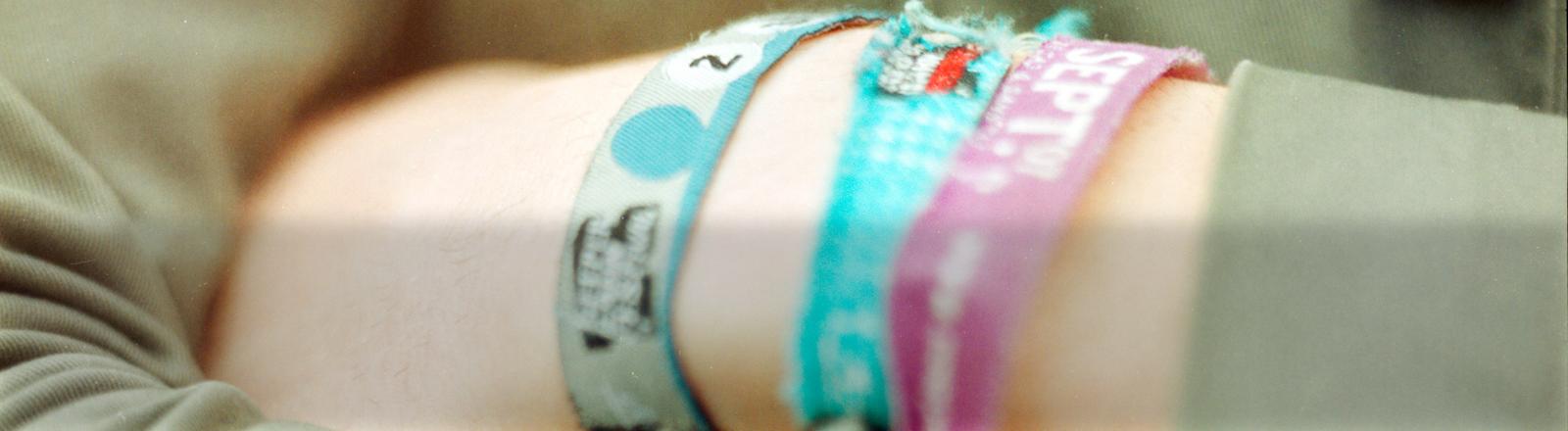 Ein Handgelenk mit verschiedenen Festivalbändchen.