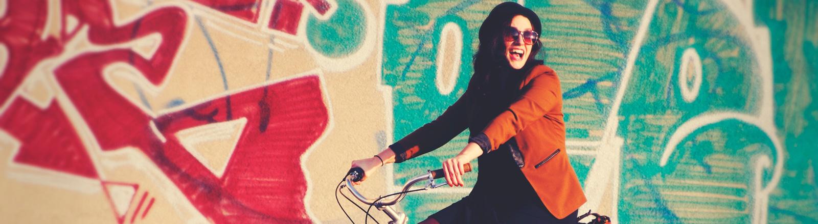 Eine fröhliche Frau auf einem Fahrrad.