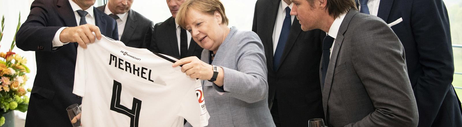 Angela Merkel mit einem Fußballtrikot der Nationalmannschaft, auf dem ihr Name steht