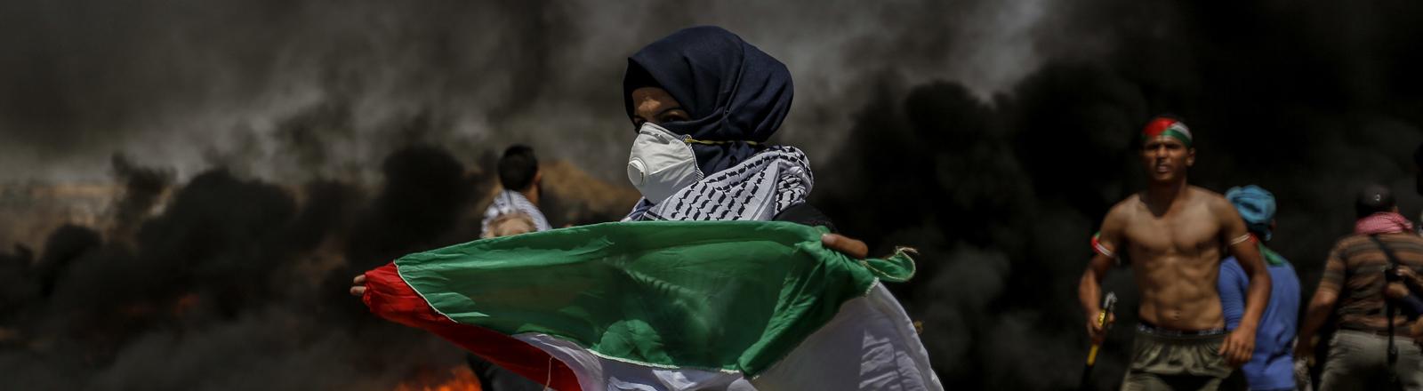 Mann mit Palästinensischer Flagge und Atemmaske, im Hintergrund Feuer und dunkler Rauch