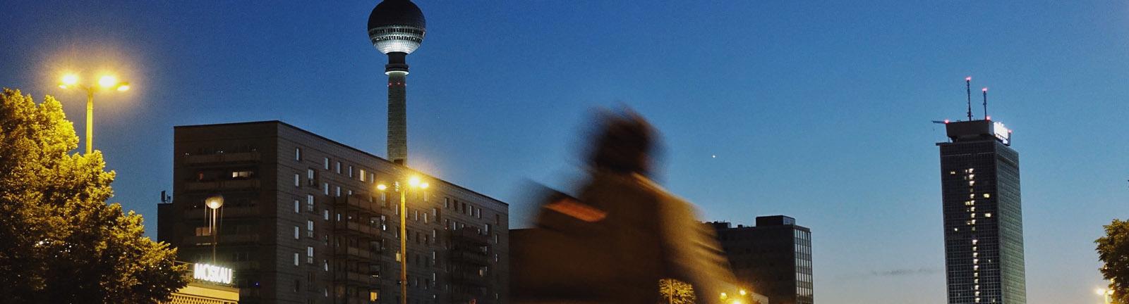 Berlin, Fahrradfahrer am Abend auf der Karl-Marx-Allee