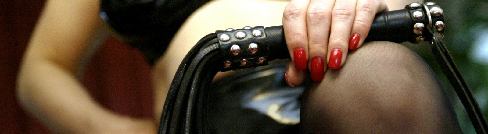 Eine Frau mit schwarzem Leder-BH hält eine Peitsche in der Hand.