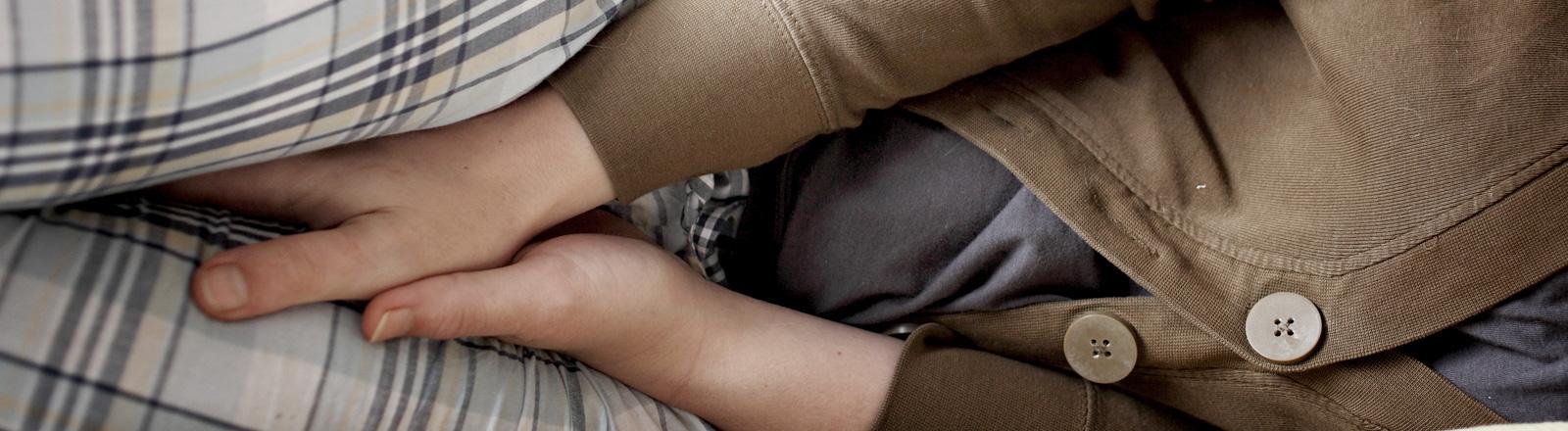 Eine Frau liegt auf der Seite und klemmt sich ihre Hände zwischen die Beine.
