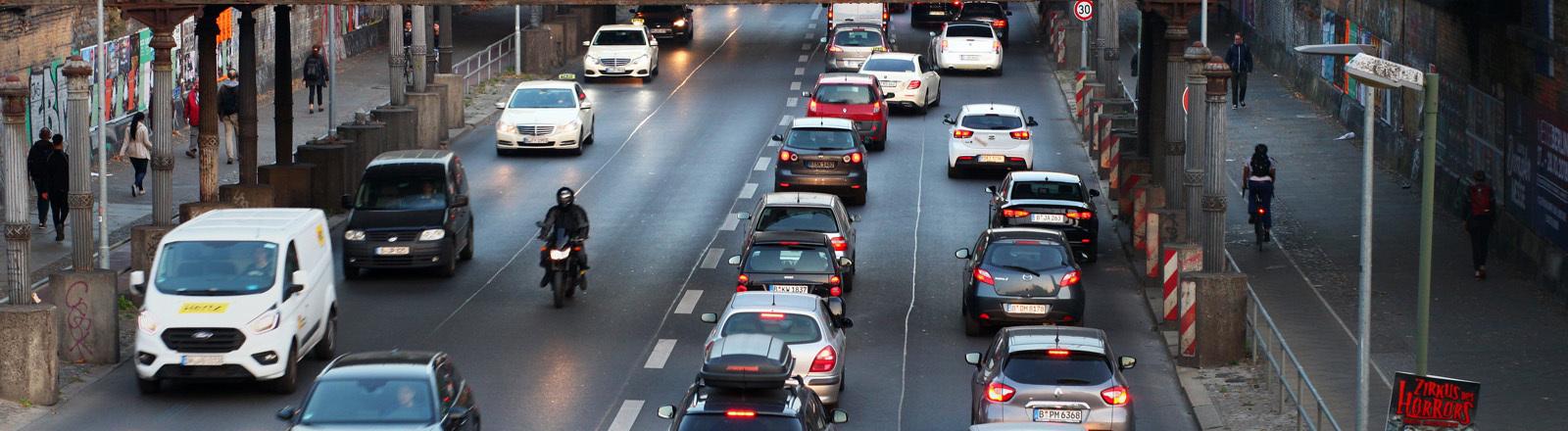 Eine befahrene Straße mit Autos, Rollerfahrer und Fußgängern.