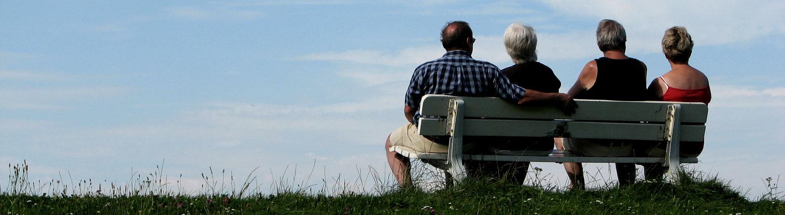 Vier Senioren sitzen auf einer Parkbank.