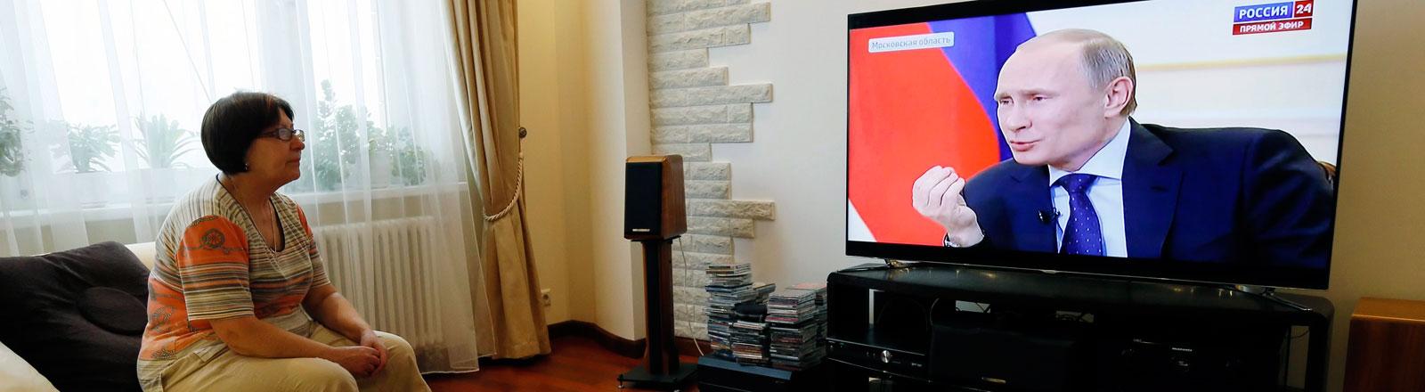Eine Frau schaut auf einen Fernseher, auf dem Präsident Putin zu erkennen ist.