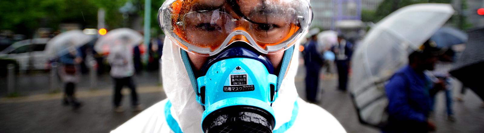 Ein Mann mit Schutzanzug, Schutzbrille und Atemmaske schaut in die Kamera, Bild: dpa