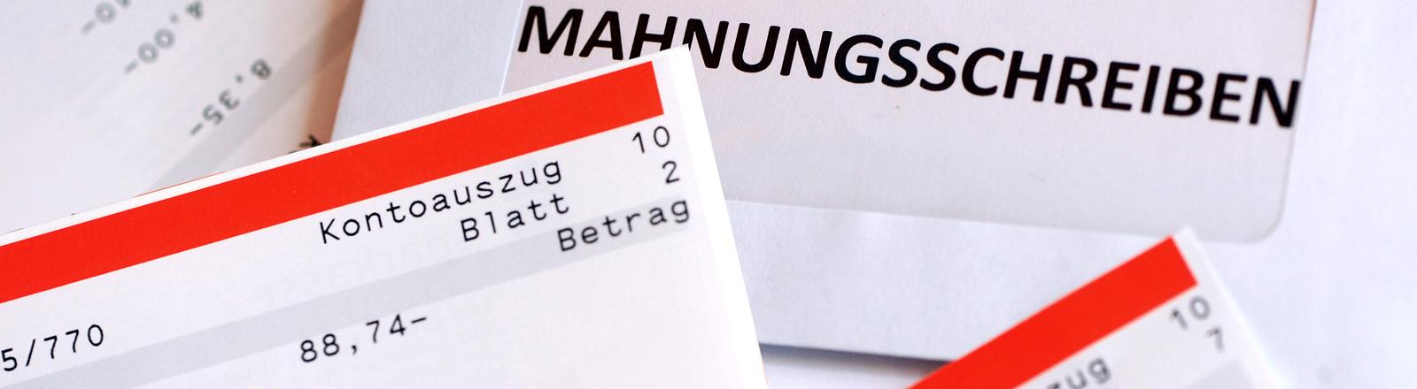 Kontoauszug, der einen Betrag von -88,74 Euro zeigt, und ein Mahnschreiben.