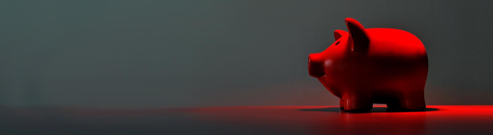 Ein rot angeleuchtetes Sparschwein