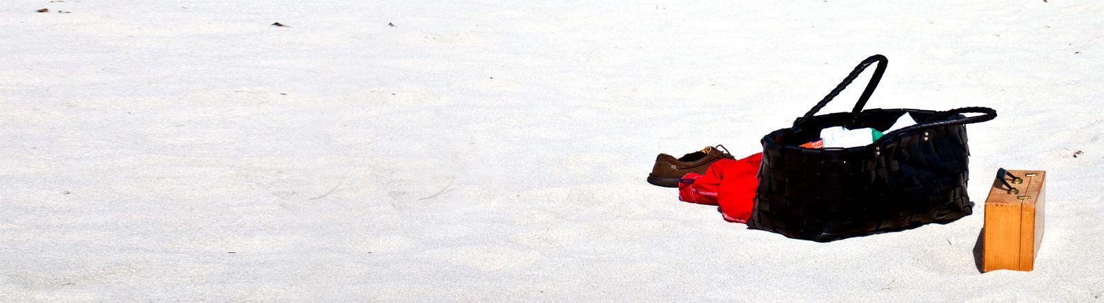 Eine Tasche und ein kleiner Koffer am Strand