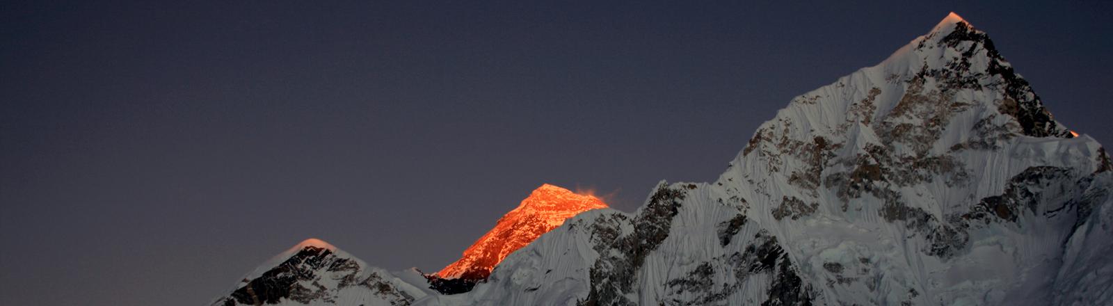 Ein Blick ins Himalaya-Gebirge mit einem rötlich angeleuchteten Gipfel.