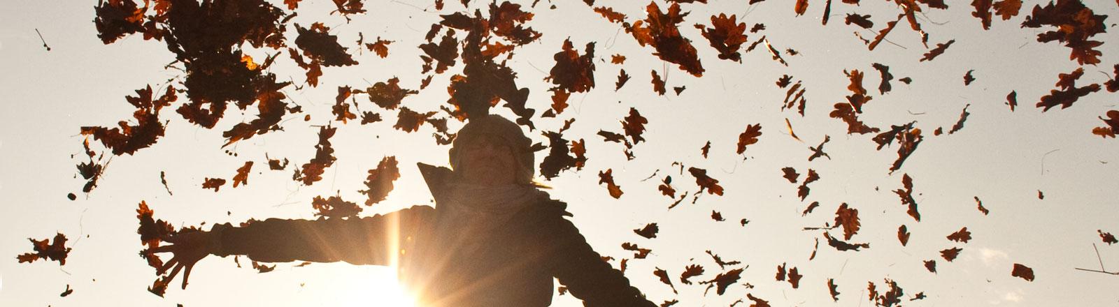 Eine Frau wirft Laub in die Luft