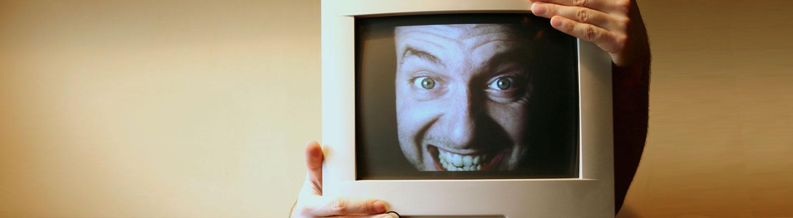 Das Gesicht eines lachenden Mannes auf einem Computerbildschirm