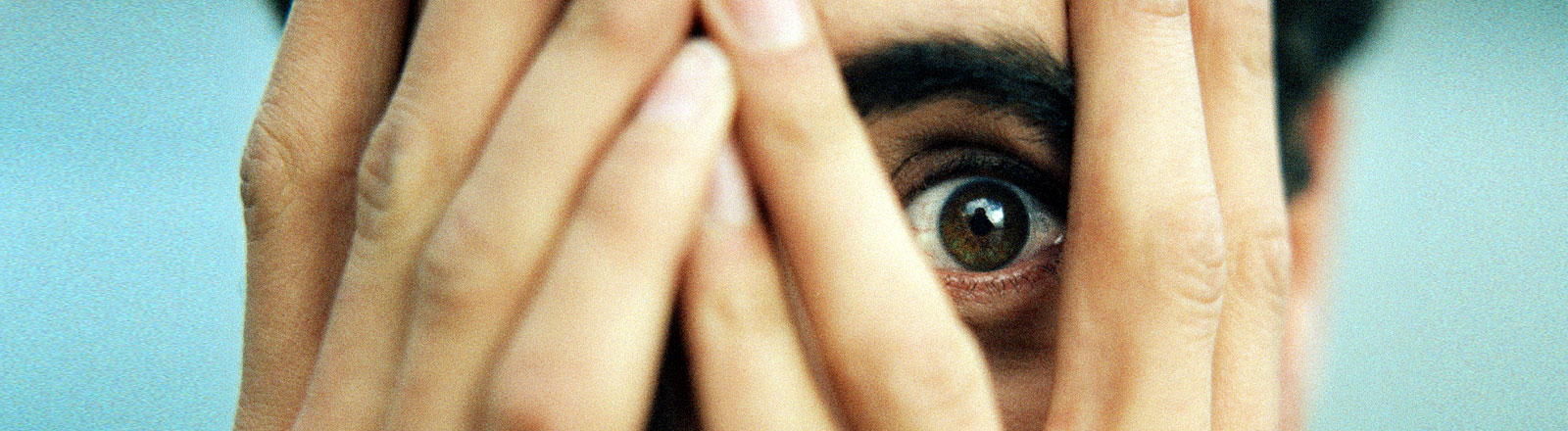Ein Mann versteckt sich hinter seinen Händen, nur sein Auge ist zu sehen.