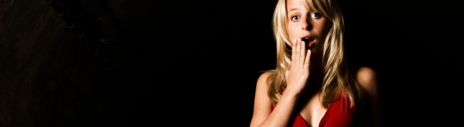 Eine Frau im roten Kleid reißt die Augen auf und hält erschrocken die Hand vor den Mund.
