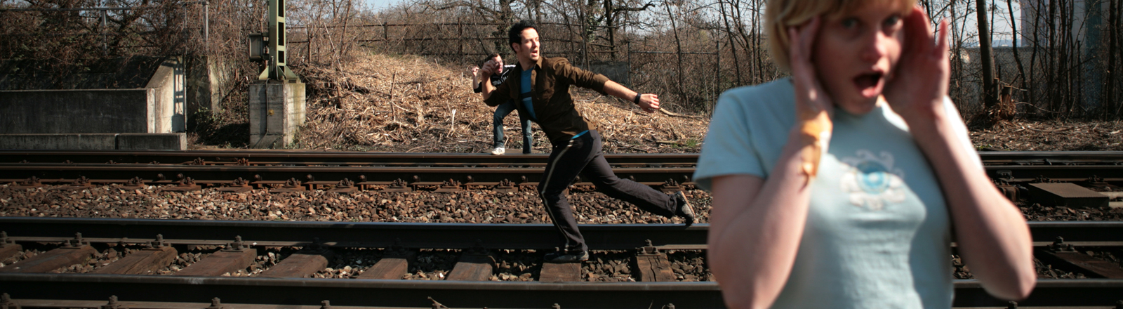 Ein Mann rennt auf einem Eisenbahngleis, eine Frau im Vordergrund schaut entsetzt.