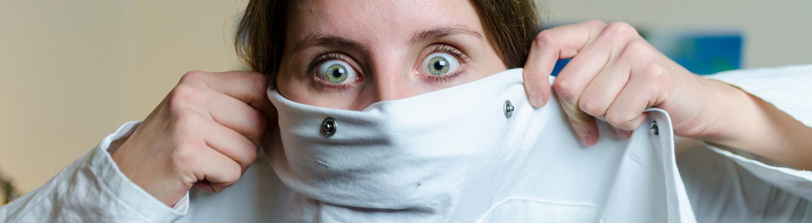 Eine Frau hält sich erschrocken ein weißes Hemd vors Gesicht und reißt die Augen auf.