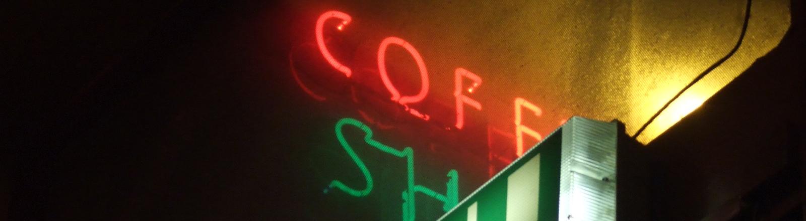 Ein Coffee-Shop-Neonlicht, darunter ein Notausgang-Schild
