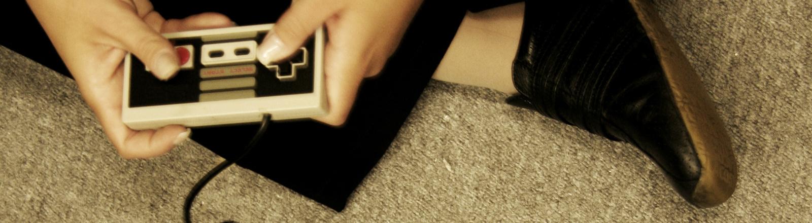Jemand sitzt auf dem Fußboden und spielt mit einem alten Controller für den Nintendo NES.