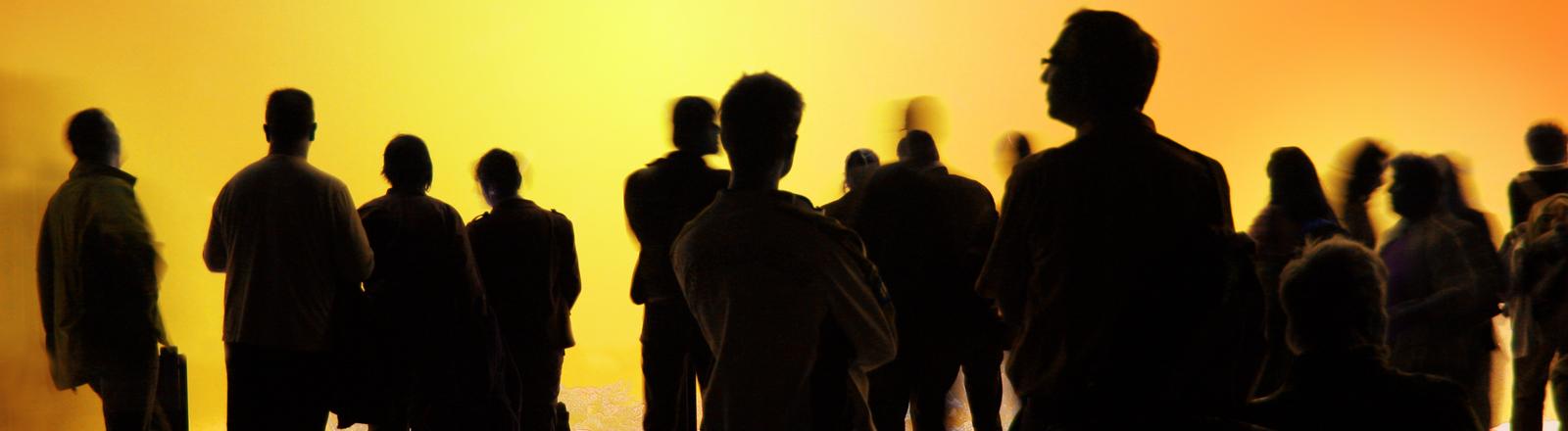 Viele Menschen stehen vor einer gelben Wand und unterhalten sich.