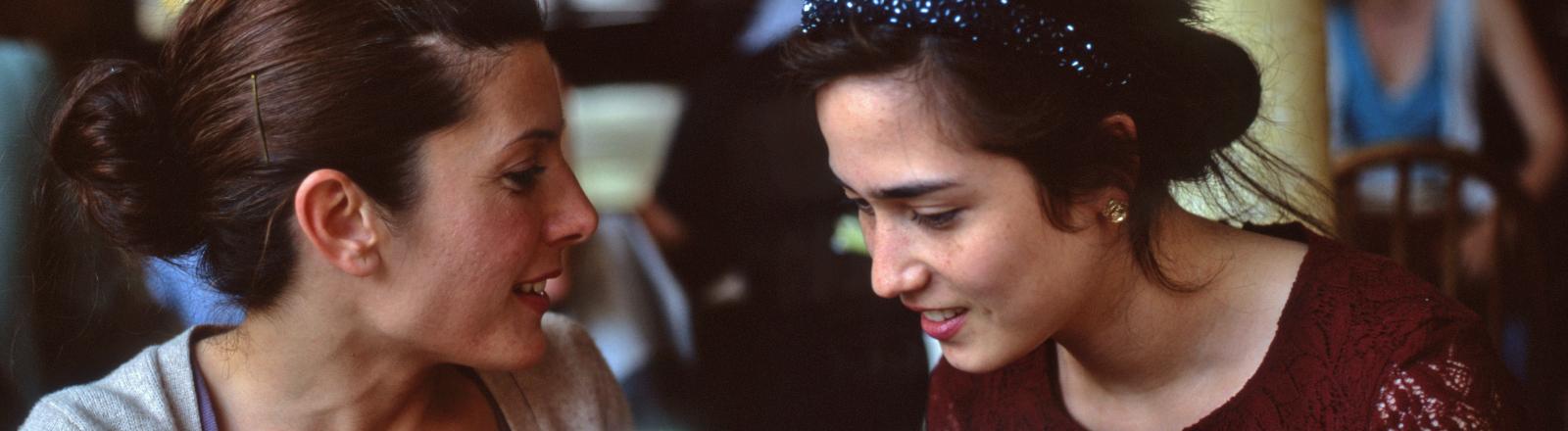 Zwei Freundinnen unterhalten sich angeregt in einem Café.