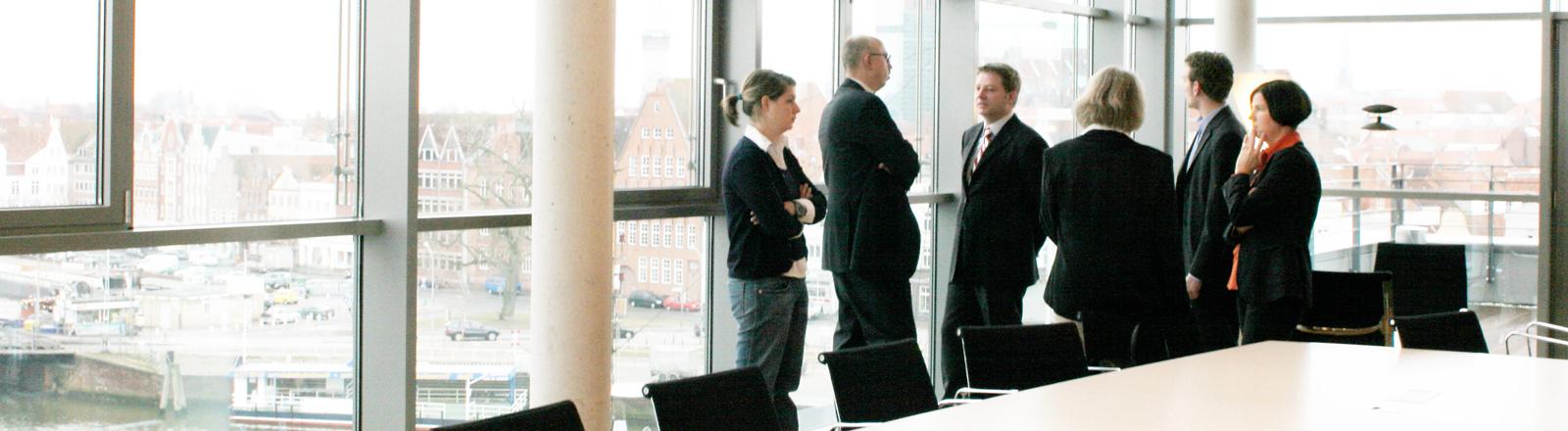 In einem Konferenzraum stehen sechs Geschäftsleute herum und starren professionell aneinander vorbei.