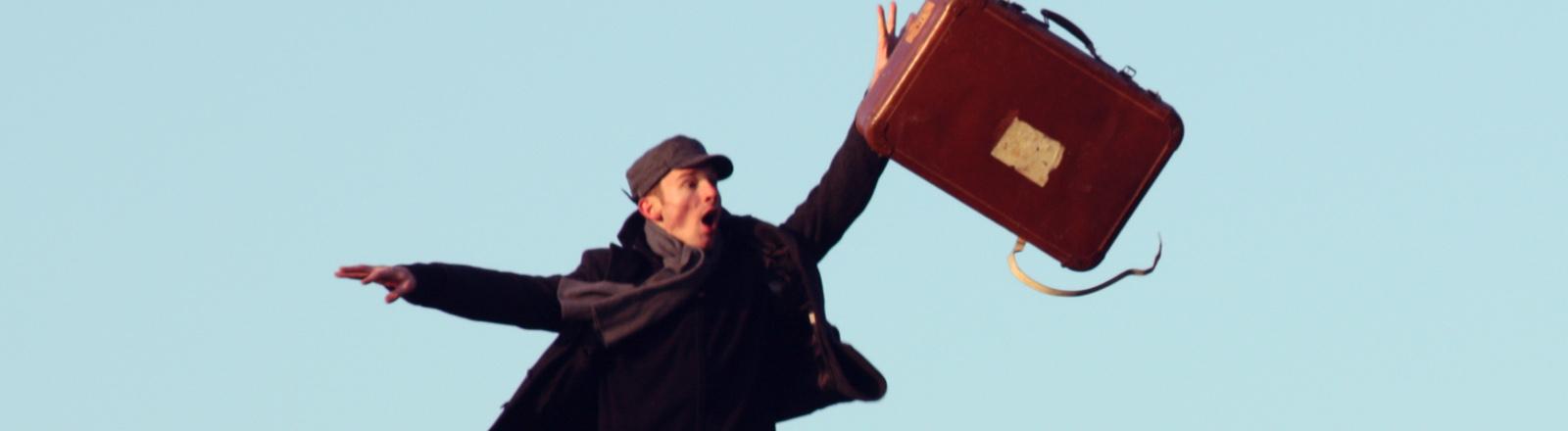 Mann mit Koffer, der in die Luft springt.