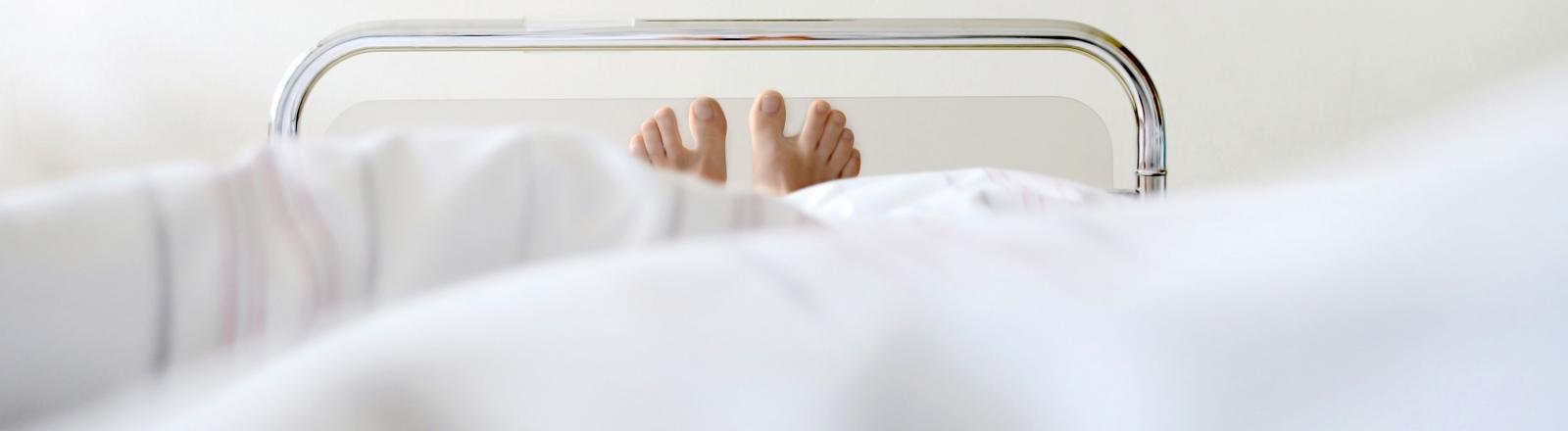 Füße die unter einer Decke im Krankenhaus-Bett hervor schauen