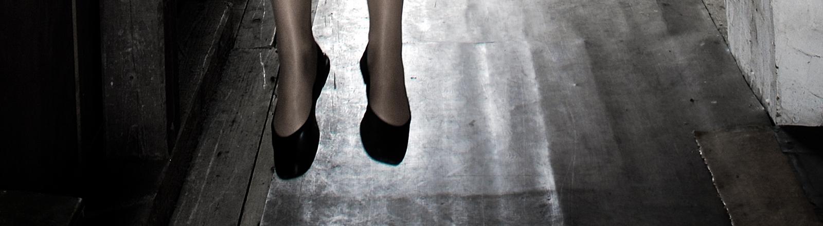 Beine einer Frau, die über dem Boden hängen