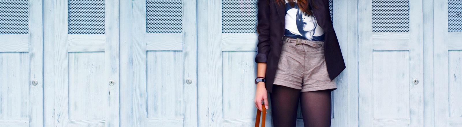 Eine junge Frau steht vor einer Wand aus Spindtüren.