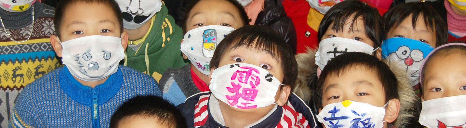 Chinesische Kinder haben Gesichtsmasken bemalt und lernen im Unterricht über den Umgang mit Smog.