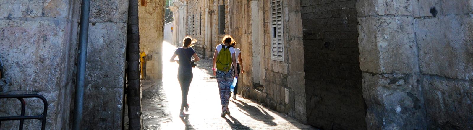 Drei junge Leute laufen im gegenlicht durch ein Stadttor in Jerusalem.