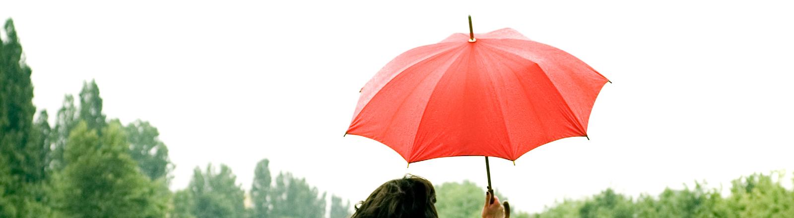 Frau mit Regenschirm in der hand