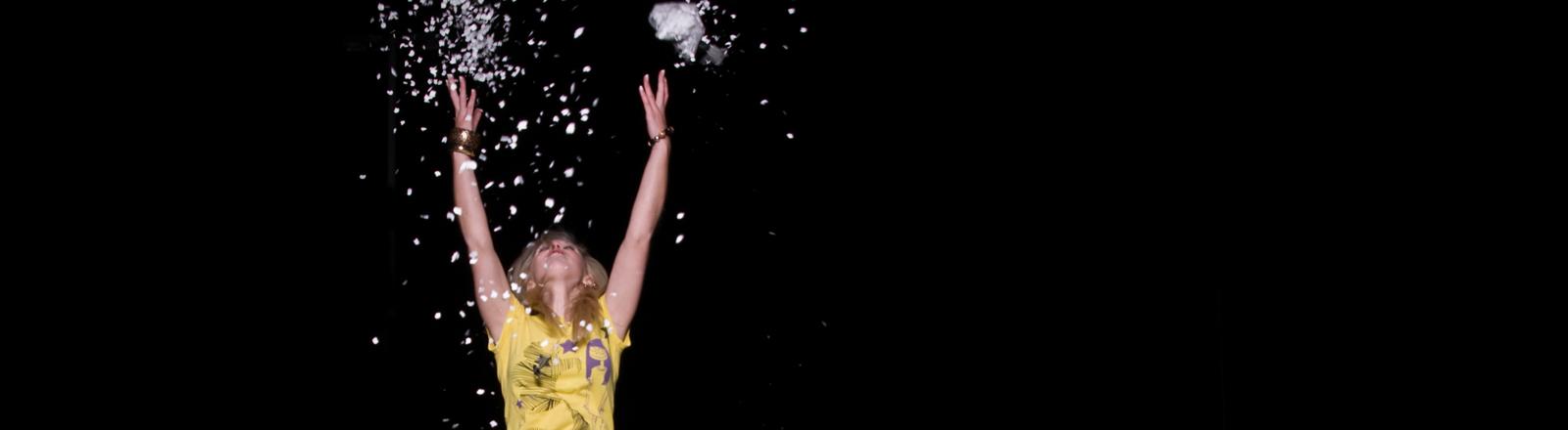 Frau im Konfetti-Regen, die beide Arme in die Luft wirft.