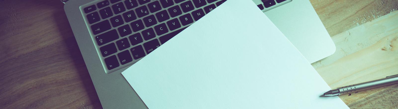Laptop und ein Blatt Papier.
