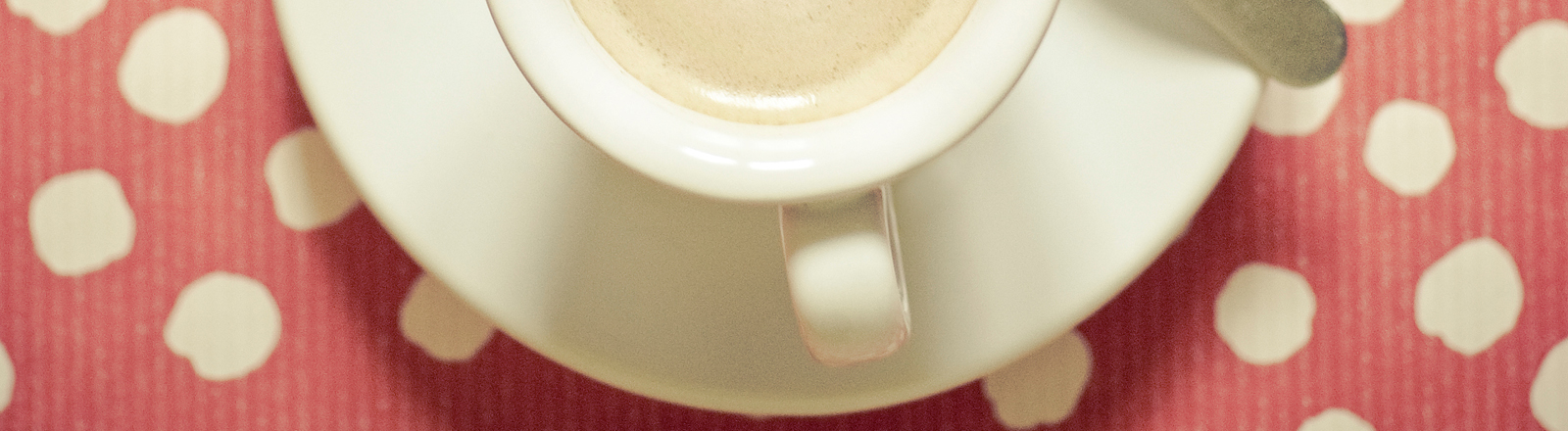 Espressotasse auf roter Tischdecke.