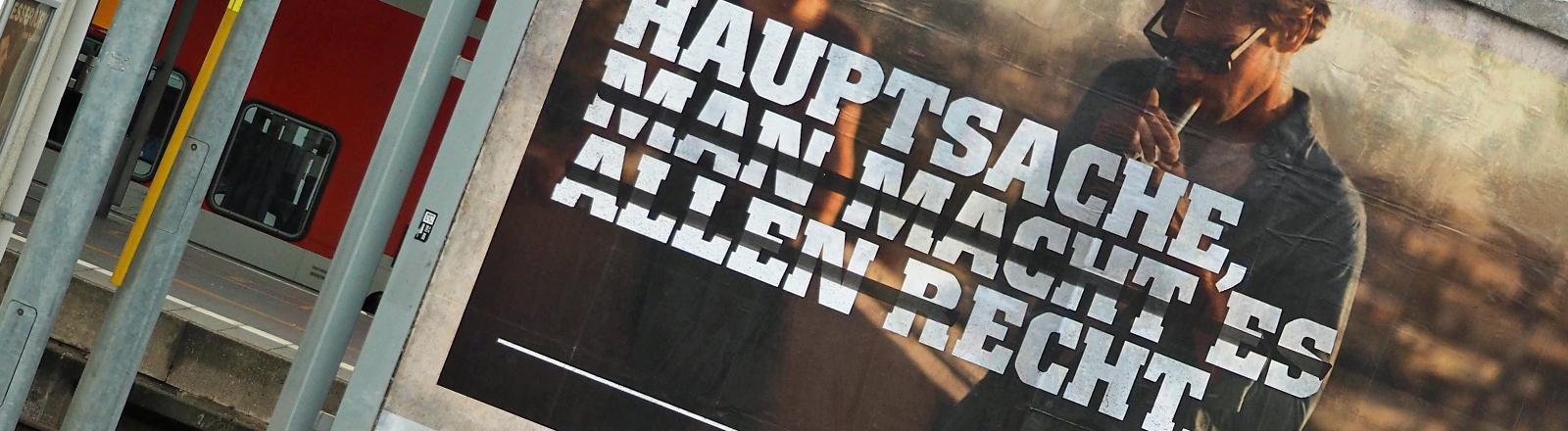 """Auf einem Bahnhof hängt ein Werbeplakat für Zigaretten: """"Hauptsache (macht macht es allen r)echt""""."""