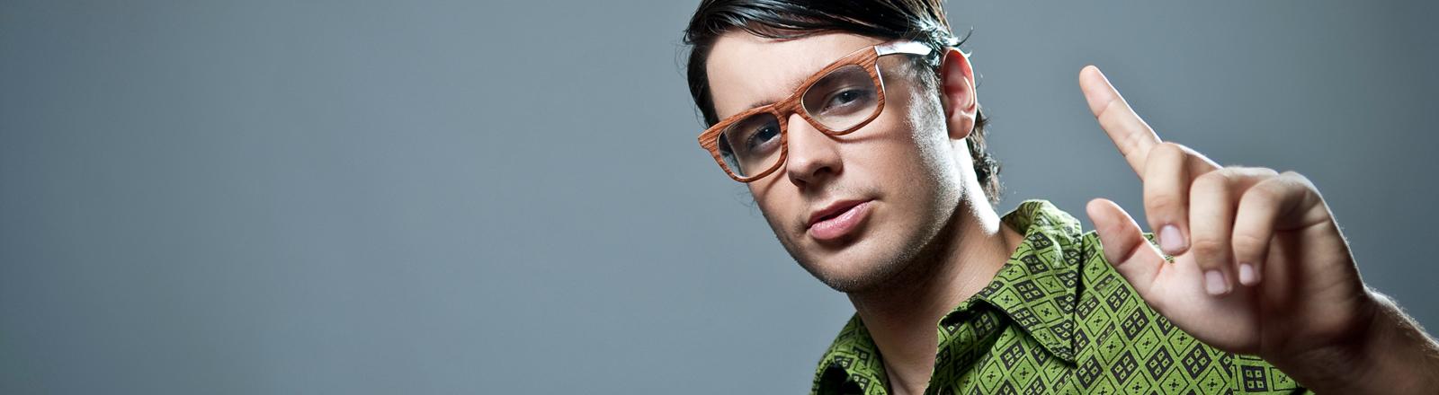 Ein Mann mit Brille hebt mahnend den Finger in die Höhe. Kurz gesagt: Ein Besserwisser, Schlaumeier, Klugscheißer.