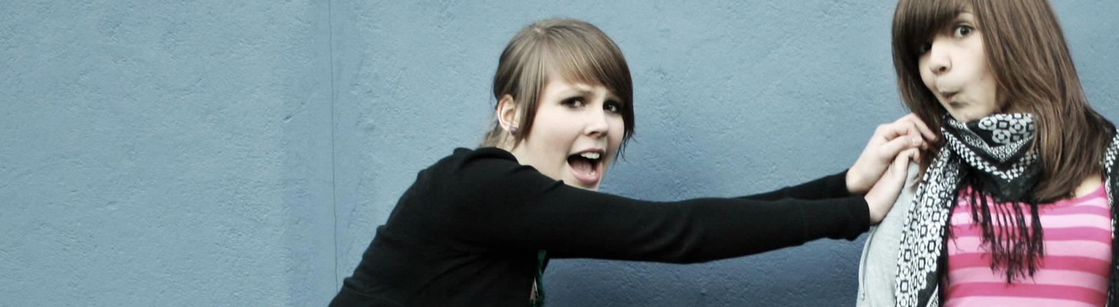 Eine junge Frau schiebt ihre Freundin aus dem Bild, die verzieht das Gesicht zu einer lustigen Grimasse.