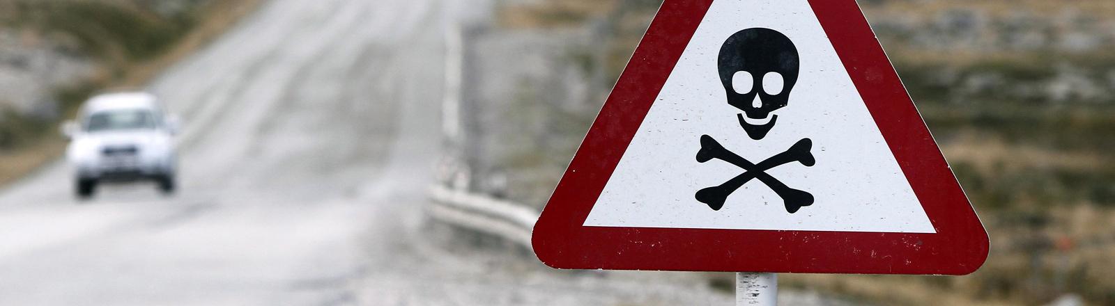 An einer Straße auf den Falkland-Inseln steht ein warnendes Schild mit Totenkopf-Symbol.