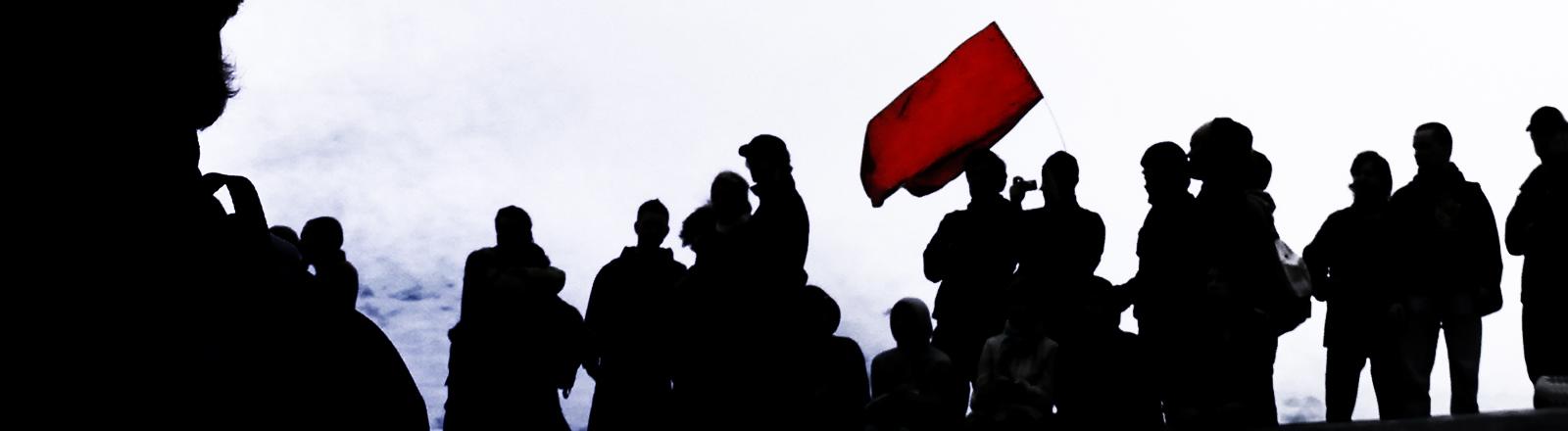 Mehrere Personen, nur als schwarze Schemen zu erkennen, haben sich unter einer roten Flagge versammelt.