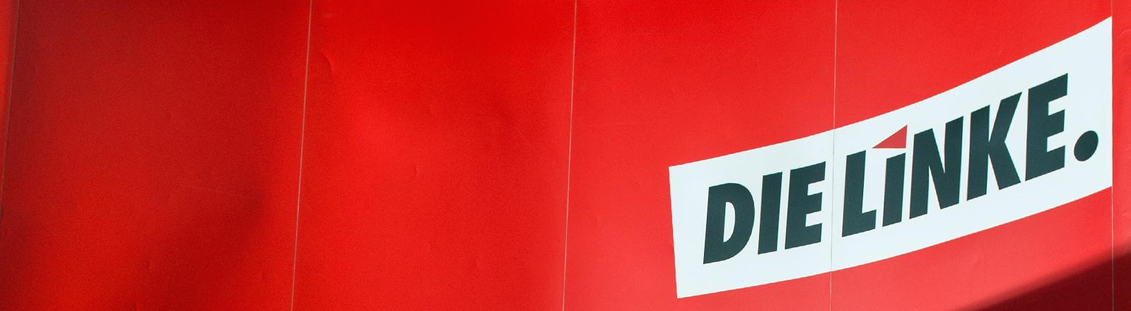 """An einer knallroten Wand steht der Schriftzug der Partei """"Die Linke.""""."""