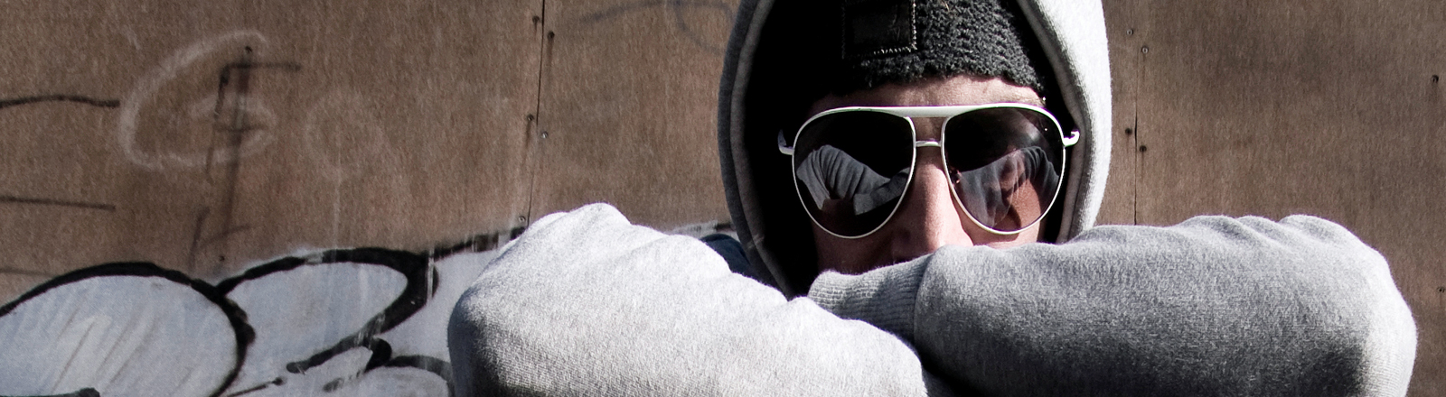 Ein Mann im Kapuzenpulli und mit Sonnenbrille.