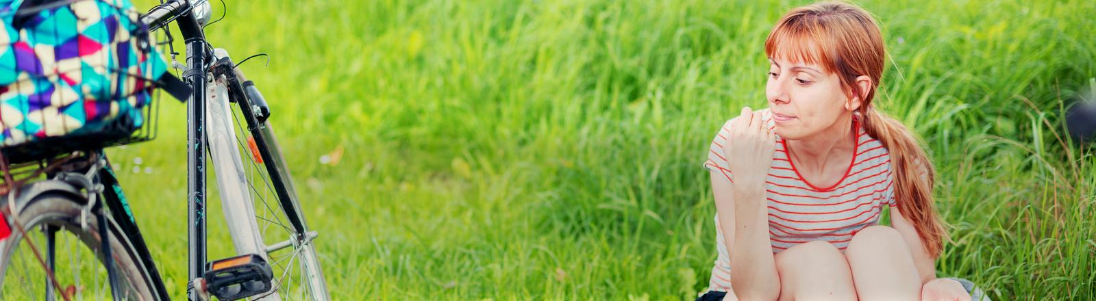 Eine Frau sitzt im Gras neben ihrem Fahrrad.